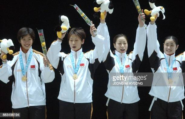Chinese gold medalist women fencers wave to photographers after the awards ceremony for the women fencing sabre team event at the14th Asian Games in...