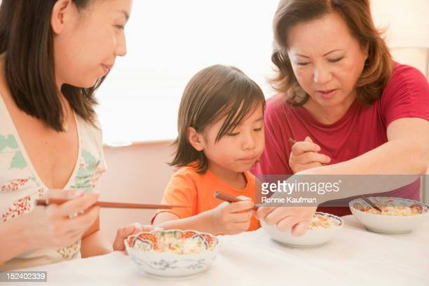 Chinese grandmother teaching grandson to use chopsticks