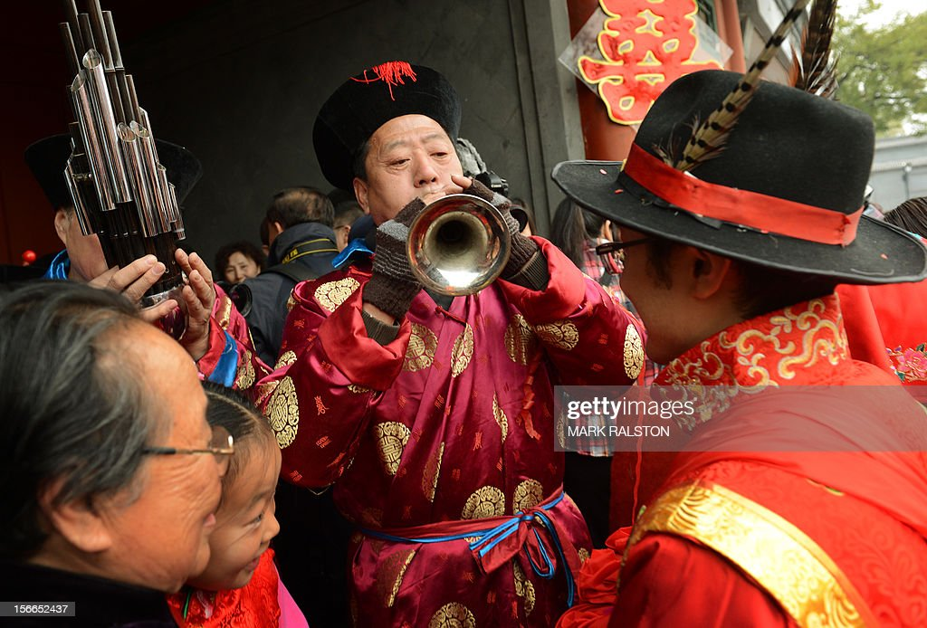 A Chinese groom listens to musicians during his wedding at a temple beside Houhai Lake in Beijing on November 18, 2012. President Hu Jintao recently called for a new Chinese growth model, marked by greater domestic demand and private enterprise, to ensure the long-term health of the world's second largest economy. AFP PHOTO/Mark RALSTON