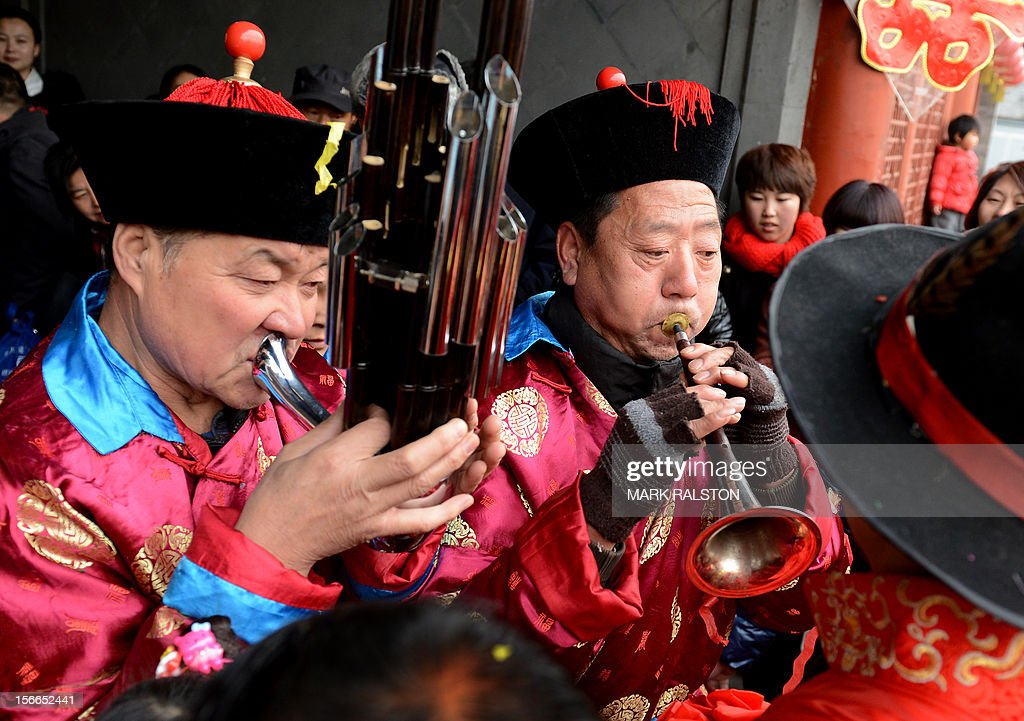 A Chinese groom (R) listens to musicians during his wedding at a temple beside Houhai Lake in Beijing on November 18, 2012. President Hu Jintao recently called for a new Chinese growth model, marked by greater domestic demand and private enterprise, to ensure the long-term health of the world's second largest economy. AFP PHOTO/Mark RALSTON