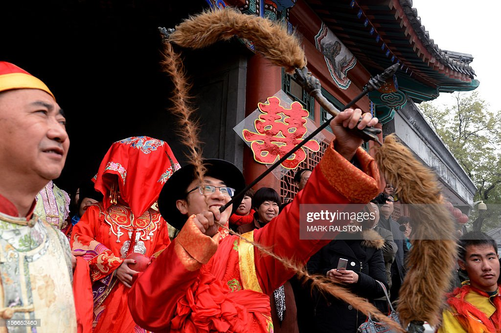 A Chinese groom shoots a symbolic arrow during his wedding at a temple beside Houhai Lake in Beijing on November 18, 2012. President Hu Jintao recently called for a new Chinese growth model, marked by greater domestic demand and private enterprise, to ensure the long-term health of the world's second largest economy. AFP PHOTO/Mark RALSTON