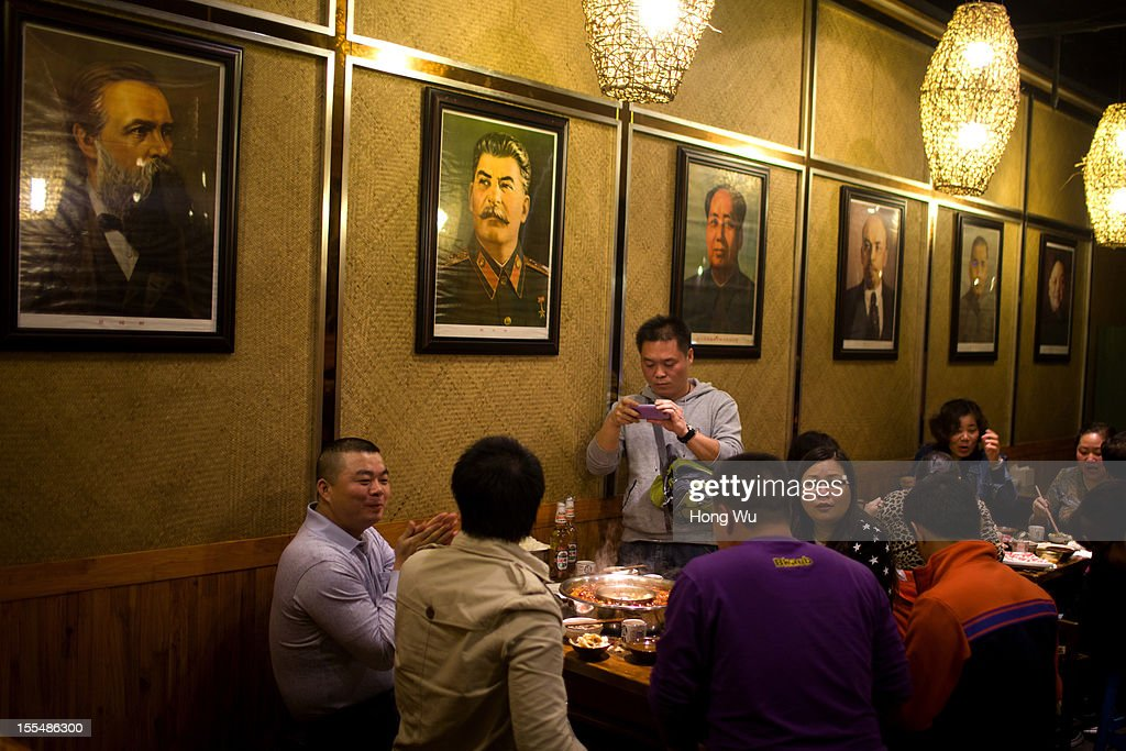 Chinese guests enjoy food as they sit under portraits of Engels, Stalin and Mao Tse-tung, Lenin, Sun Yat Sen and Deng Xiaoping at a chafing dish restaurant on November 4, 2012 in Chongqing, China. This theme restaurant, which was built in 2005, displays special Chinese red revolution culture of the 1970s that attracts customers with their old style decoration style and red revolution atmosphere.