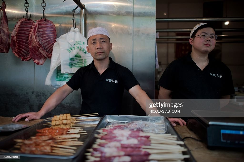 A Chinese halal butcher waits for customers during the Muslim fasting month of Ramadan in Beijing on July 1, 2016. Muslims fasting in the month of Ramadan must abstain from food, drink and sex from down to dusk, when they break the fast with a meal known as Iftar. / AFP / NICOLAS