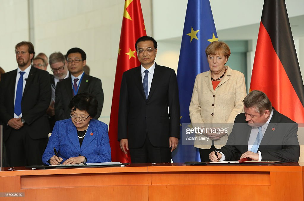 Chinese Health and Family Planning Minister <a gi-track='captionPersonalityLinkClicked' href=/galleries/search?phrase=Li+Bin&family=editorial&specificpeople=227305 ng-click='$event.stopPropagation()'>Li Bin</a> (L) and German Health Minister <a gi-track='captionPersonalityLinkClicked' href=/galleries/search?phrase=Hermann+Groehe&family=editorial&specificpeople=6400355 ng-click='$event.stopPropagation()'>Hermann Groehe</a> (CDU) (first row) sign a contract in front of <a gi-track='captionPersonalityLinkClicked' href=/galleries/search?phrase=Li+Keqiang&family=editorial&specificpeople=2481781 ng-click='$event.stopPropagation()'>Li Keqiang</a>, premier of the People's Republic of China and party secretary of the State Council (second row L), and German Chancellor <a gi-track='captionPersonalityLinkClicked' href=/galleries/search?phrase=Angela+Merkel&family=editorial&specificpeople=202161 ng-click='$event.stopPropagation()'>Angela Merkel</a> (second row R) during a signing ceremony during German-Chinese government consultations on October 10, 2014 in Berlin, Germany. The visit is Li's second visit to the country, China's biggest European trade partner, since taking office last year. During the consultations, companies from the two countries' telecommunications, automotive, and alternative energy industries signed agreements.