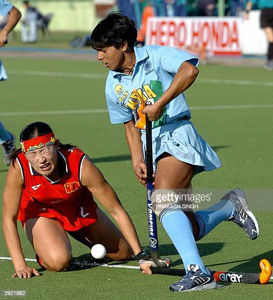 Chinese hockey player Huang Xuejiao tackles India's Saba Anjum during a league match of the 5th Women's Asia Hockey Cup in New Delhi 02 February 2004...