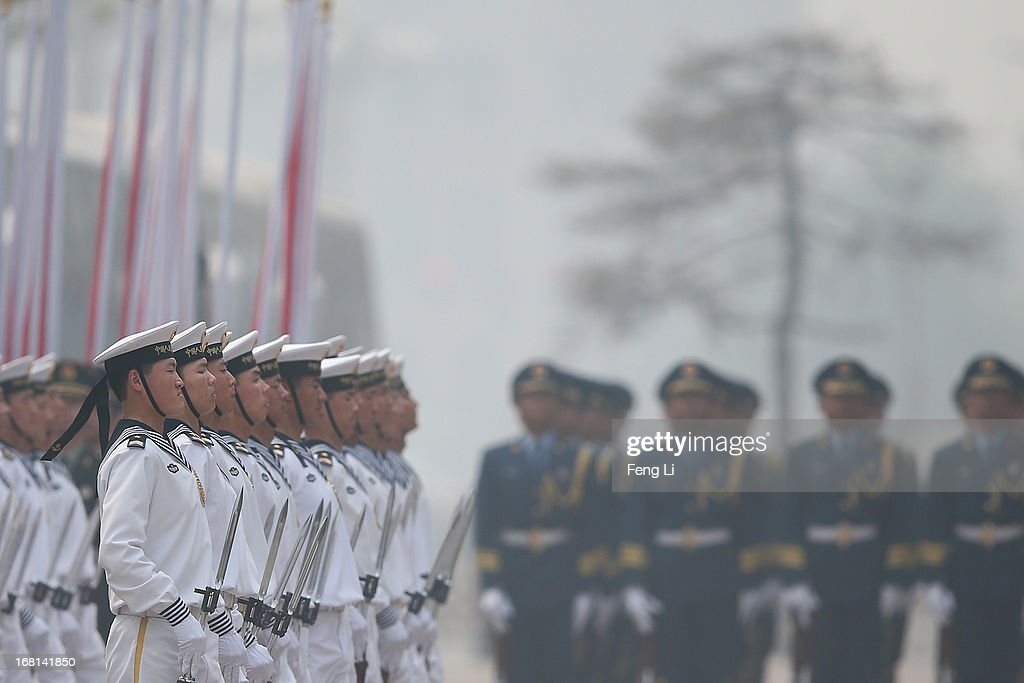 Chinese honor guards adjust their attire during severe pollution before a welcome ceremony for visiting Palestinian President Mahmoud Abbas outside the Great Hall of the People on May 6, 2013 in Beijing, China.
