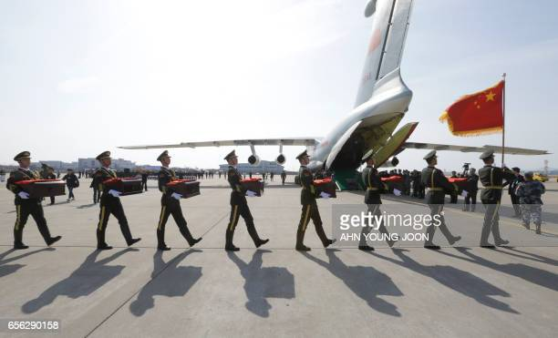 Chinese honor guards carry caskets containing the remains of Chinese soldiers into a cargo airplane during the handing over ceremony at the Incheon...