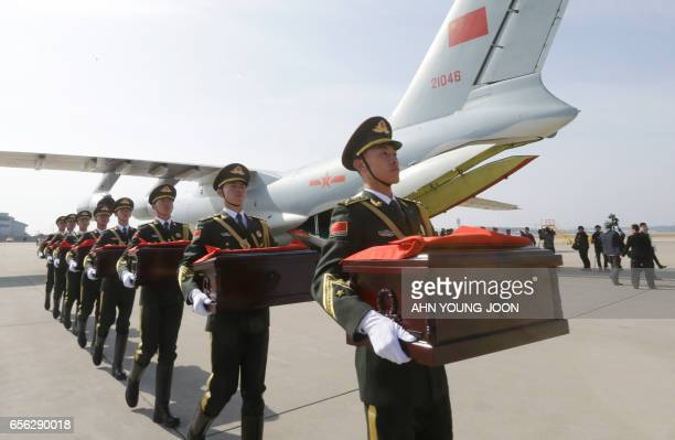 Chinese honor guards with caskets containing the remains of Chinese soldiers move into a cargo airplane during the handing over ceremony at the...