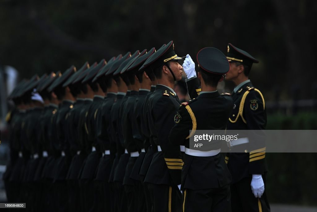 A Chinese honour guard (2nd-R) uses a string to make sure guards stand in line before the arrival of Sri Lankan President Mahinda Rajapaksa outside the Great Hall of the People in Beijing on May 28,2013. Mahinda Rajapaksa is on a two-day visit to China.
