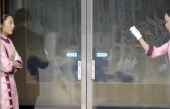 A Chinese hostess cleans the glass door as her colleague looks on during a meeting between Chinese Vice Prime Minister Wang Qishan and French Foreign...