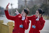 Chinese hostesses use a mobile phone to take a photo during the third session of the 12th National People's Congress outside the Great Hall of the...