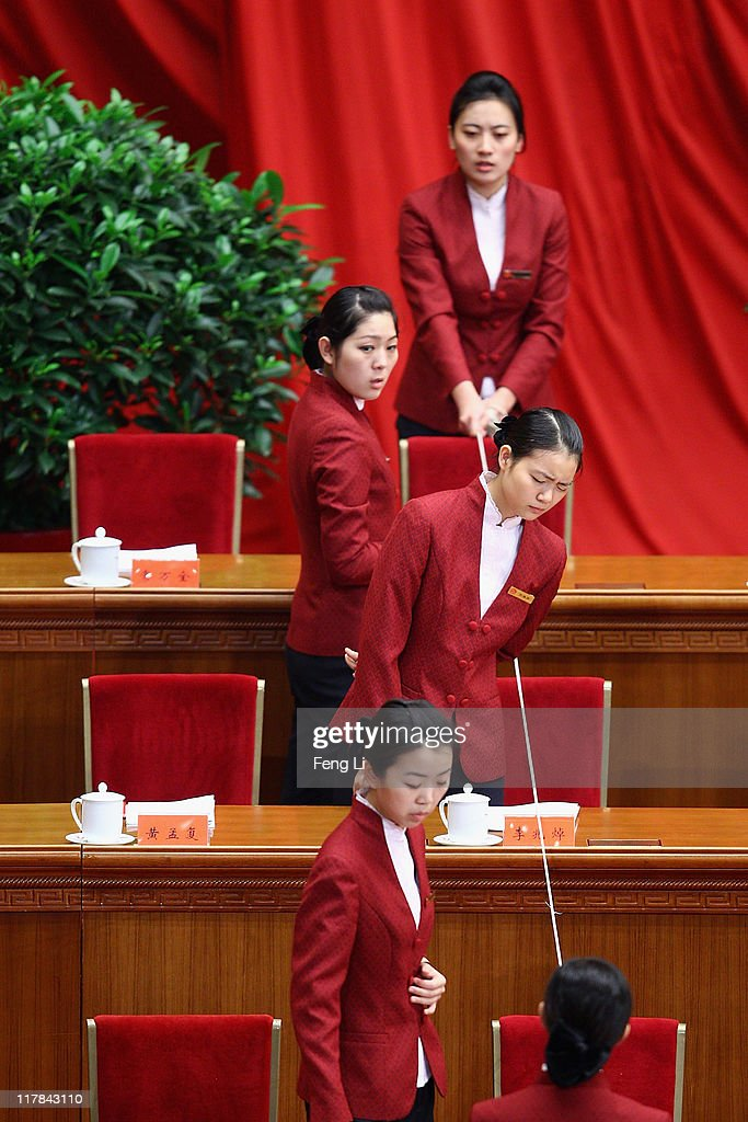 Chinese hostesses use a string to align tea cups in preparation for the celebration of the Communist Party's 90th anniversary at the Great Hall of the People on July 1, 2011 in Beijing, China.