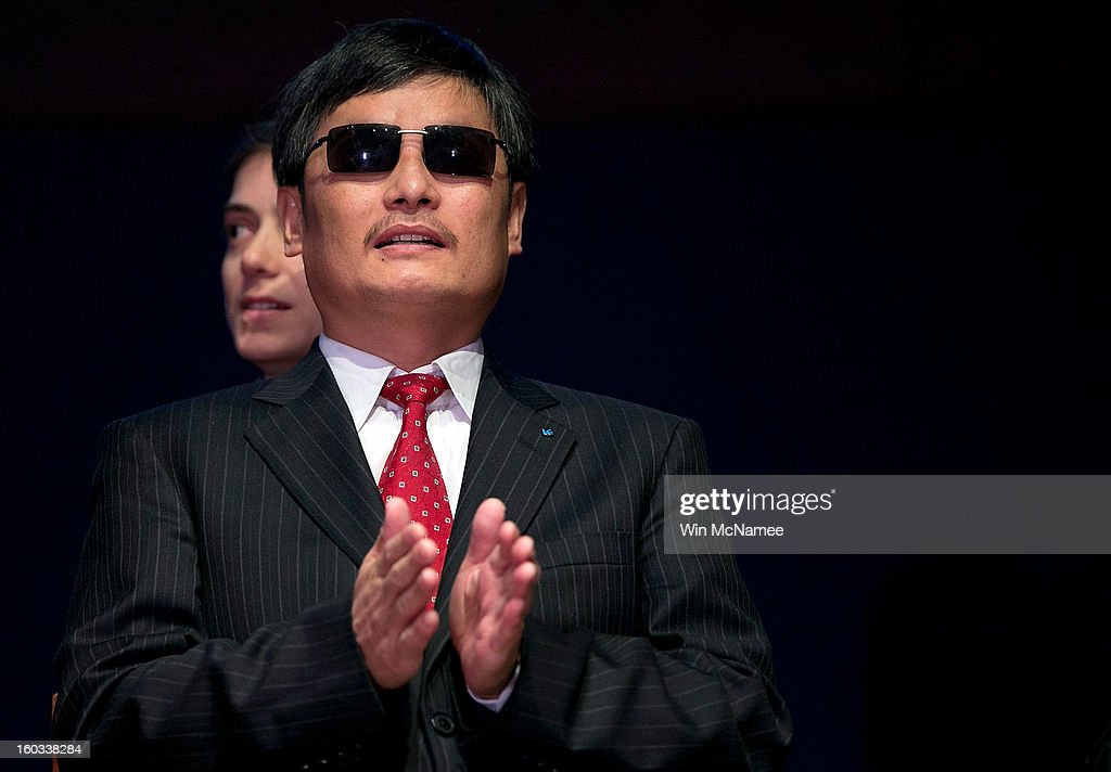 Chinese human rights activist Chen Guangcheng applauds during a ceremony where he was presented the Tom Lantos Human Rights Prize January 29 2013 in...