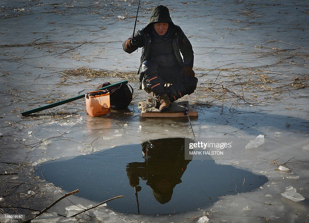 A Chinese ice fisherman tries his luck in minus 3 Centigrade temperatures in the frozen Houhai Lake of Beijing on December 9, 2012. The fisherman, who were hoping to catch carp, share the lake with swimmers and ice skaters. AFP PHOTO/Mark RALSTON