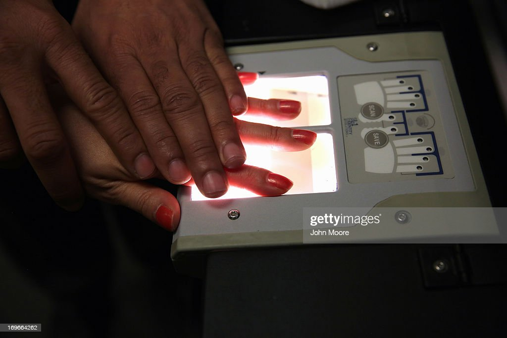 A Chinese immigrant is fingerprinted during her 'biometrics' appointment to receive a green card at the U.S. Citizenship and Immigration Services (USCIS) Queens office on May 30, 2013 in the Long Island City neighborhood of the Queens borough of New York City. The branch office is located in an area heavily populated by immigrants and processes thousands of green card and U.S. citizenship applications each year.