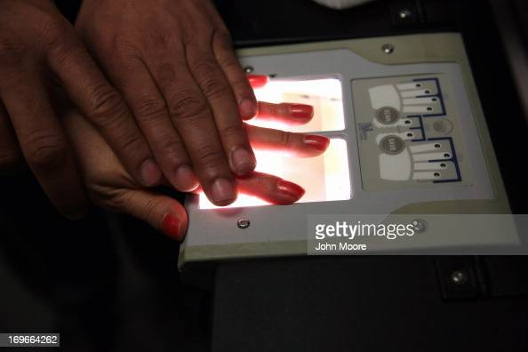 Chinese immigrant is fingerprinted during her 'biometrics' appointment to receive a green card at the US Citizenship and Immigration Services Queens...