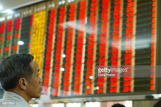A Chinese investor looks at an electronic board displaying share prices at a securities company June 3 2005 in Guangzhou of Guangdong Province China...