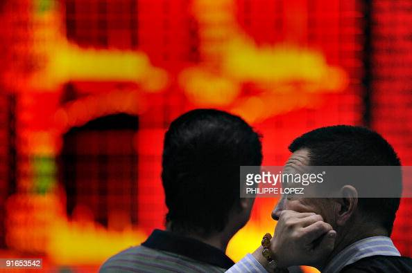 A Chinese investor monitors screens showing stock indexes at a trading house in Shanghai on October 9 2009 Chinese shares closed up 476 percent...