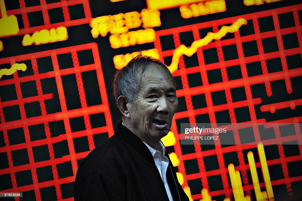 A Chinese investor stands in front of a screen showing stock indexes at a trading house in Shanghai on October 9 2009 Chinese shares closed up 476...