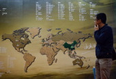 A Chinese investor walks past an investment map showing suitable property markets for wealthy Chinese to invest in at the International Property Expo...
