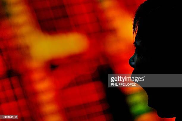 A Chinese investor yawns a she monitors screens showing stock indexes at a trading house in Shanghai on October 9 2009 Chinese shares closed up 476...