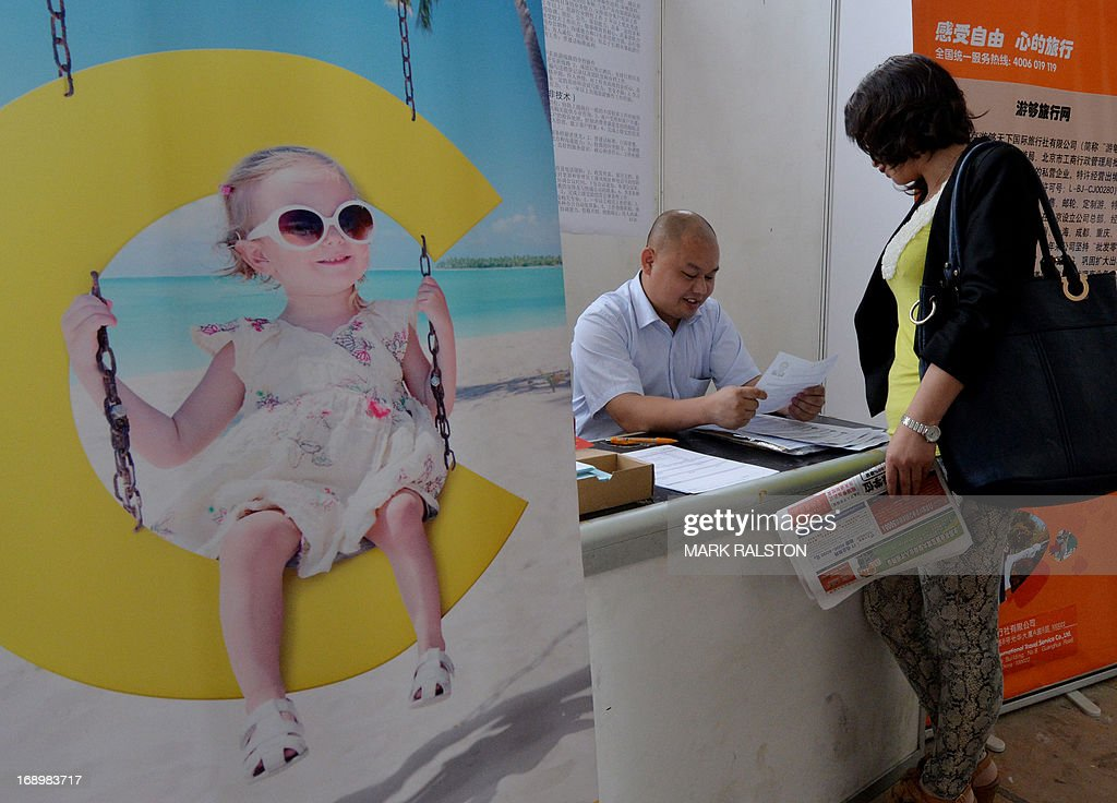 A Chinese jobseeker (R) attends a jobs fair in Beijing on May 18, 2013. Chinese state media has reported that the China will need to find employment for a record number (seven million) of college graduates this year as the country's economy continues to slow. AFP PHOTO / Mark RALSTON