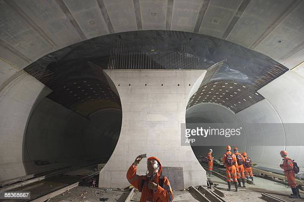A chinese journalist takes a picture of the 57kilometre railway tunnel under construction in the Alps at Sedrun on May 6 2009 The new St Gotthard...