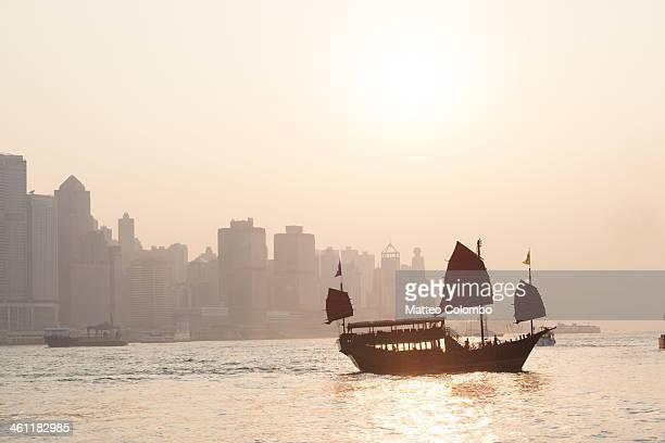 Chinese junk sail at sunset in Hong Kong harbor