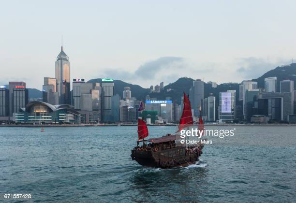 Chinese Junk sailing across the Victoria harbor between Kowloon and Hong Kong island
