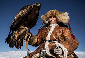 Chinese Kazakh eagle hunter holds his bird as he rides on his way to a local competition on January 29 2015 in the mountains of Qinghe County...