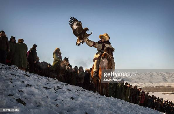 Chinese Kazakh eagle hunter releases his bird as spectators look on during a local competition on January 30 2015 in the mountains of Qinghe County...
