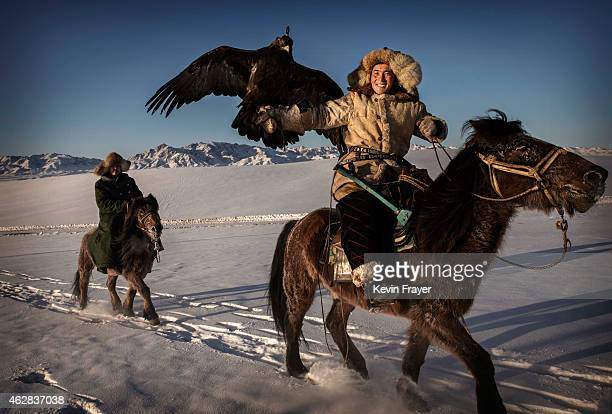 Chinese Kazakh eagle hunter rides with his eagle as he arrives for a local competition on January 30 2015 in the mountains of Qinghe County Xinjiang...