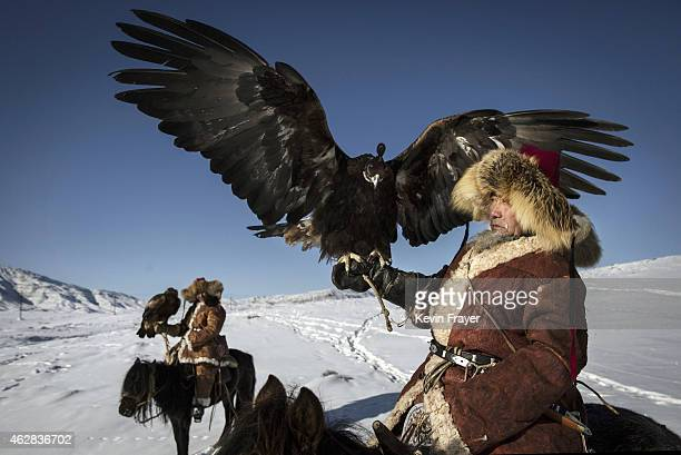 Chinese Kazakh eagle hunters sit on horseback as they travel to a local competition on January 29 2015 in the mountains of Qinghe County Xinjiang...