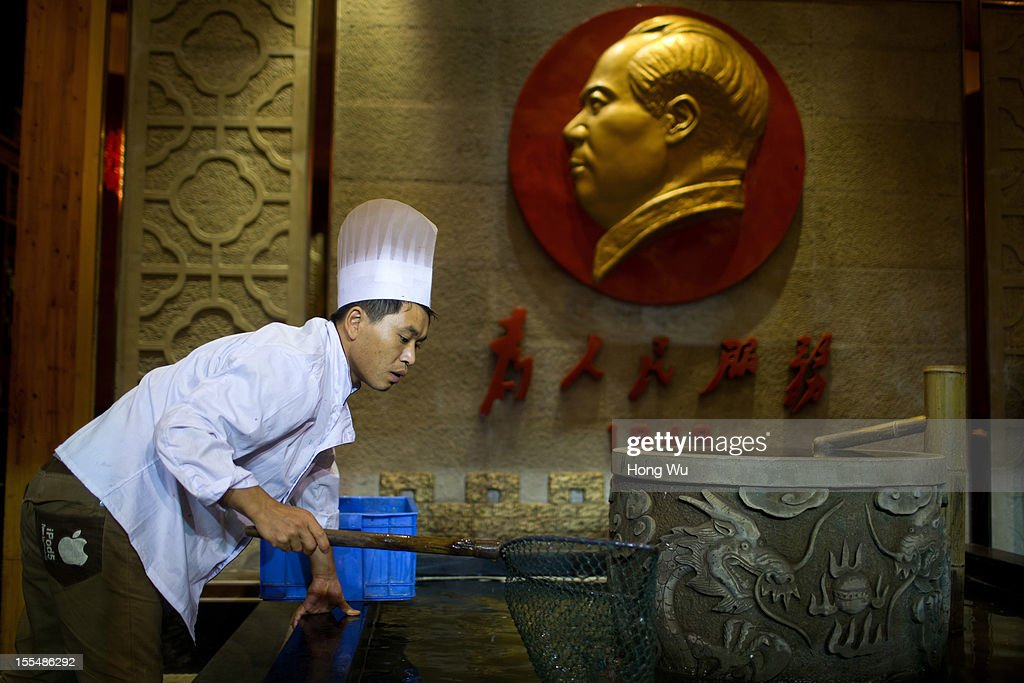 A Chinese kitchener catches fish beside a statue of Mao Tse-tung at a chafing dish restaurant on November 4, 2012 in Chongqing, China. This theme restaurant, which was built in 2005, displays special Chinese red revolution culture of the 1970s that attracts customers with their old style decoration style and red revolution atmosphere.