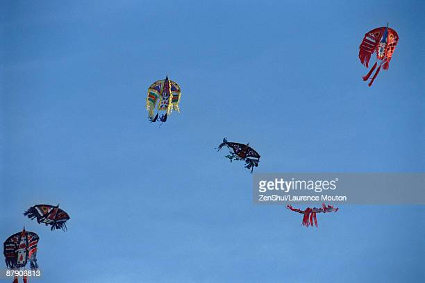 Chinese kites flying high against clear blue sky