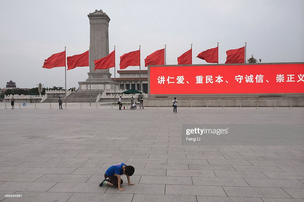 A Chinese kneels in Tiananmen Square on June 4, 2014 in Beijing, China. Twenty-five years ago on June 4, 1989 Chinese troops cracked down on pro-democracy protesters and in the clashes that followed scores were killed and injured.