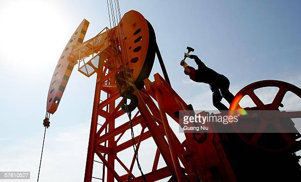 Chinese laborer repairs an oil pumping unit at Huabei oil field on May 13 2006 on the outskirts of Hejian city Hebei province China China the second...