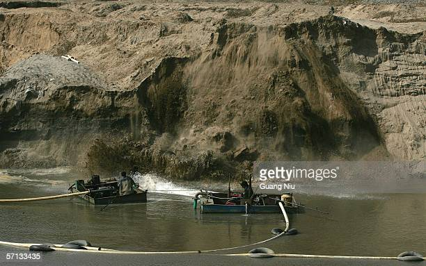 Chinese laborers extract sand from dirt along the river bank March 19 2006 on the outskirts of Beijing China The sand that they mine will be used to...
