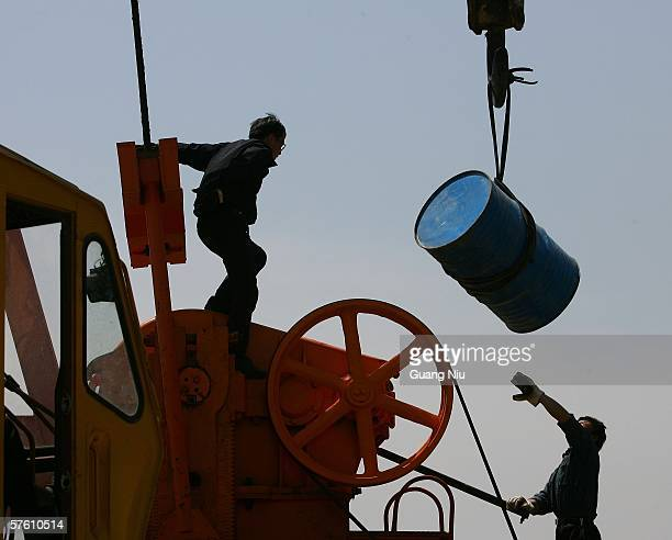 Chinese laborers repair an oil pumping unit at Huabei oil field on May 13 2006 on the outskirts of Hejian city Hebei province China China the second...