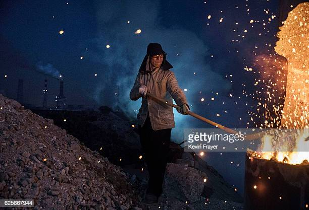 Chinese labourer loads coal into a furnace as he works at an unauthorized steel factory on November 3 2016 in Inner Mongolia China To meet China's...