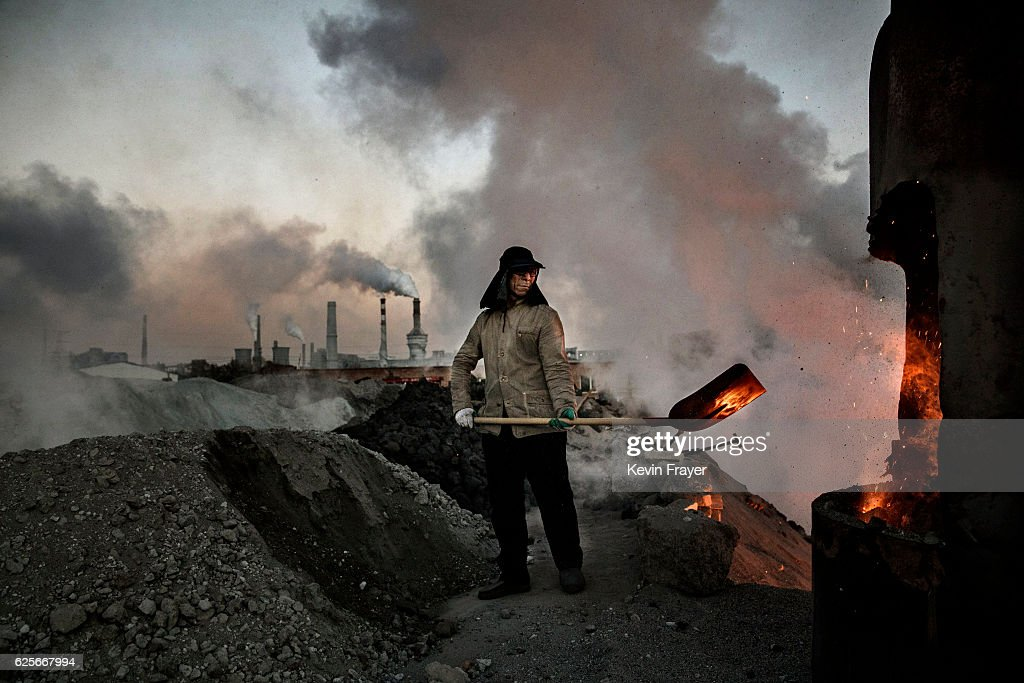 A Chinese labourer loads coal into a furnace as smoke and steam rises from an unauthorized steel factory on November 3, 2016 in Inner Mongolia, China. To meet China's targets to slash emissions of carbon dioxide, authorities are pushing to shut down privately owned steel, coal, and other high-polluting factories scattered across rural areas. In many cases, factory owners say they pay informal 'fines' to local inspectors and then re-open. The enforcement comes as the future of U.S. support for the 2015 Paris Agreement is in question, leaving China poised as an unlikely leader in the international effort against climate change. U.S. president-elect Donald Trump has sent mixed signals about whether he will withdraw the U.S. from commitments to curb greenhouse gases that, according to scientists, are causing the earth's temperature to rise. Trump once declared that the concept of global warming was 'created' by China in order to hurt U.S. manufacturing. China's leadership has stated that any change in U.S. climate policy will not affect its commitment to implement the climate action plan. While the world's biggest polluter, China is also a global leader in establishing renewable energy sources such as wind and solar power.