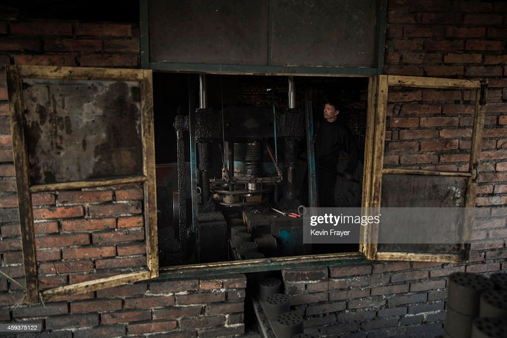 Chinese labourer works at a coal briquette depot which manufactures coal for cooking and heating on November 21 2014 in Hebei outside Beijing China...