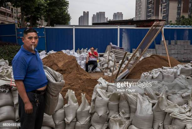 Chinese labourers bag sand at a construction site for a new development on May 14 2017 in Wuhan Hubei province China