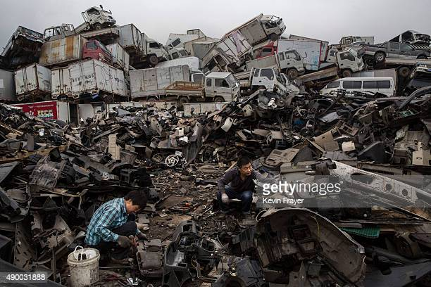 Chinese labourers dismantle pieces of vehicles taken off the road by authorities at an auto scrapyard on September 25 2015 in Zhejiang China The...