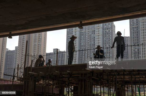 Chinese labourers work at a construction site for a new development on May 15 2017 in Wuhan Hubei province China