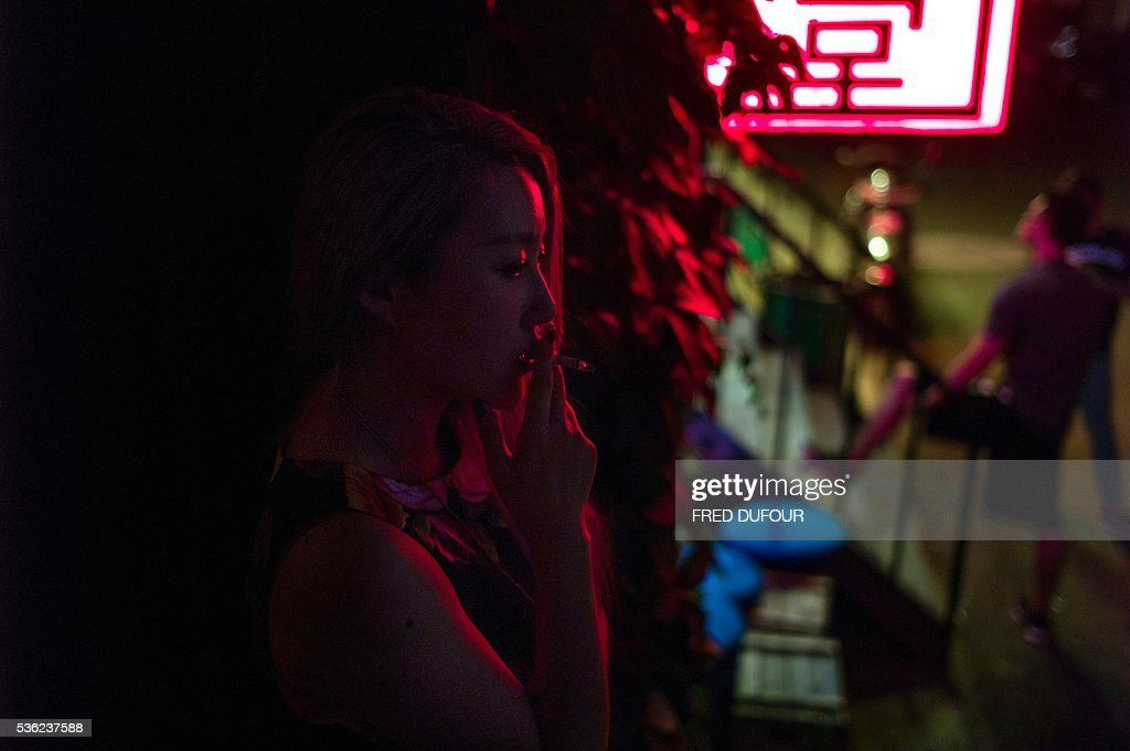 A Chinese lady smokes a cigarette outside of a bar as June 1st marks the one year anniversary of Beijing's indoor smoking ban, on May 31, 2016, in Beijing. / AFP / FRED