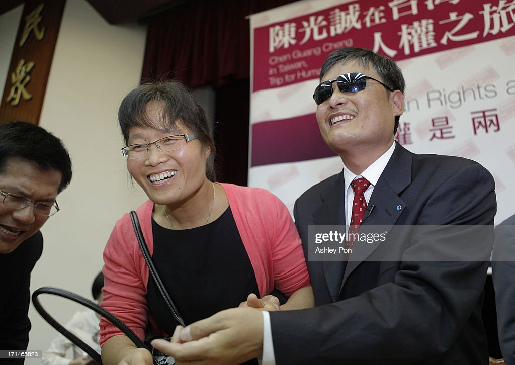 Chinese lawyer and human rights activist Chen Guangcheng and his wife Yuan Weijing shake hands with a supporter at the Legislative Yuan on June 25...