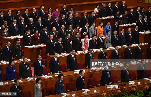 Chinese leaders including President Xi Jinping sing the national anthem during the opening session of the National People's Congress in the Great...
