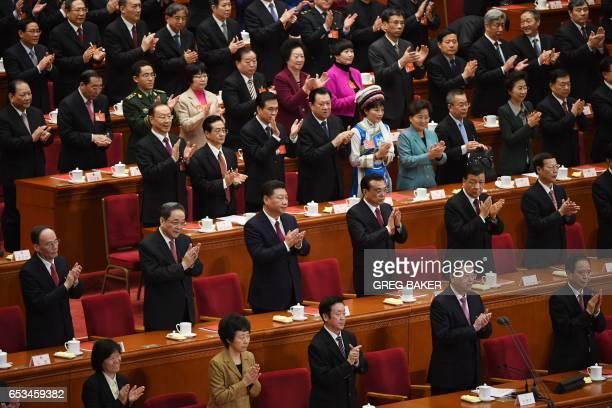 Chinese leaders including Wang Qishan Yu Zhengsheng President Xi Jinping Premier Li Keqiang Liu Yunshan and Zhang Gaoli applaud during the closing...