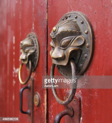 Chinese lion door knockers on red doors